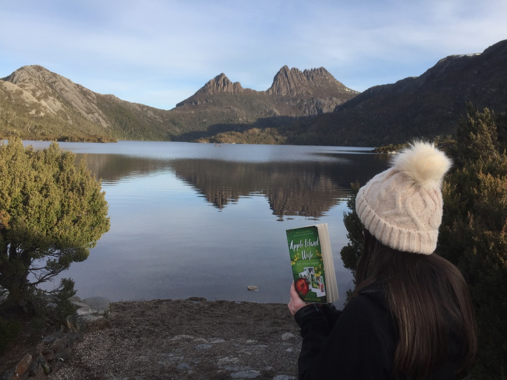 A girl reads a copy of Apple Island Wife by Fiona Stocker, at Cradle Mountain in Tasmania.