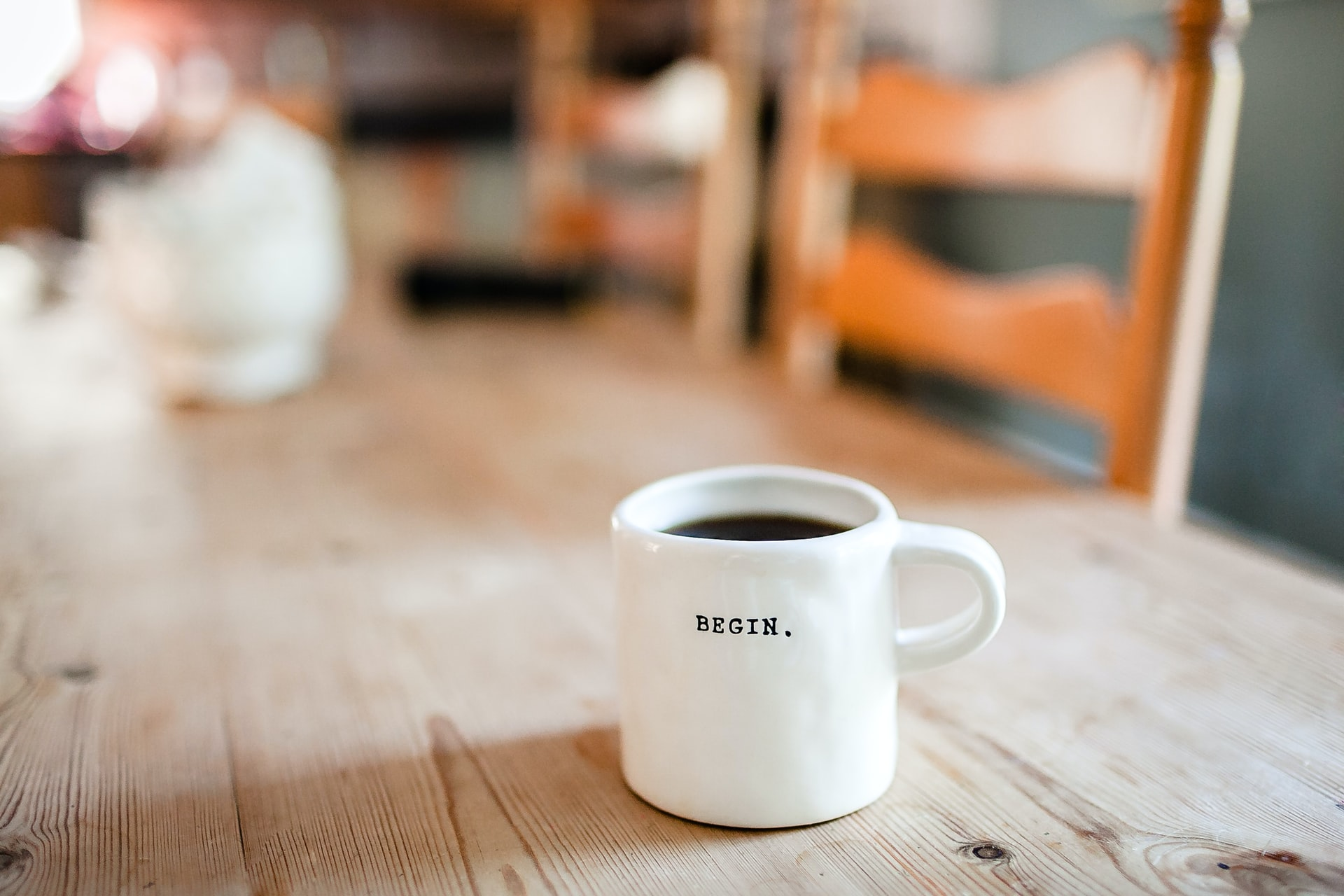 A mug sits on a table, with the word 'BEGIN' printed on it