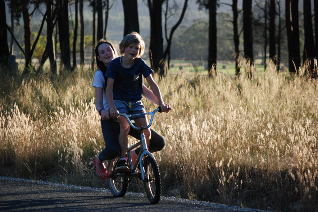 Two children ride on a bike on a rural road in Tasmania in late afternoon sunshine