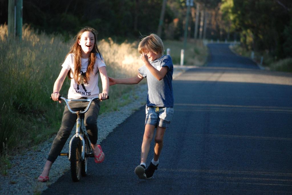 Two children ride a bike and run along a rural road in Tasmania.