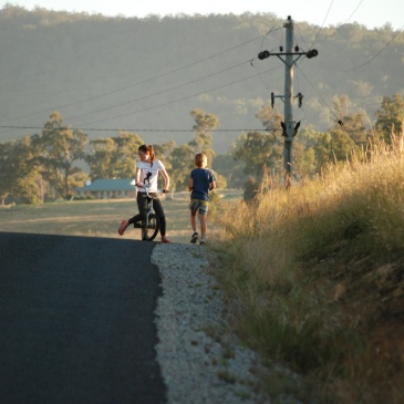Two children ride bikes and walk on a rural road in Tasmania in the late afternoon sunshine