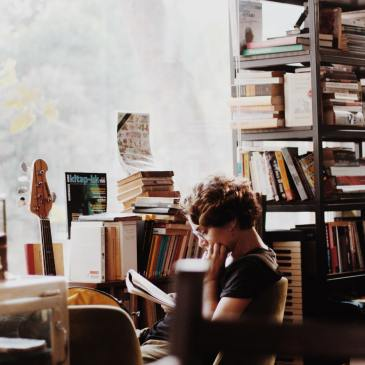A young woman sits in a room full of books, reading a notebook
