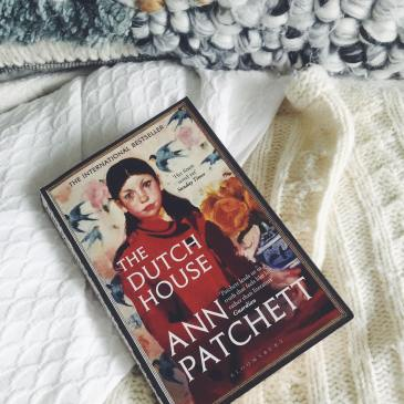 The Dutch House by Ann Patchett lies on a beautifully made up bed